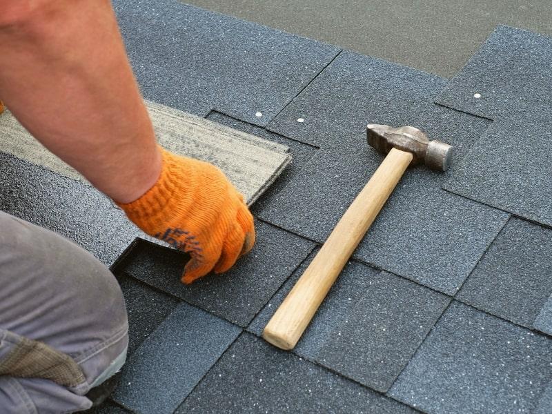 charpentier en train de poser une tuile d ardoise sur un toit