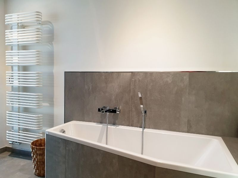 Renovation d une salle de bain avec un seche serviette et une baignoire par homy conseil