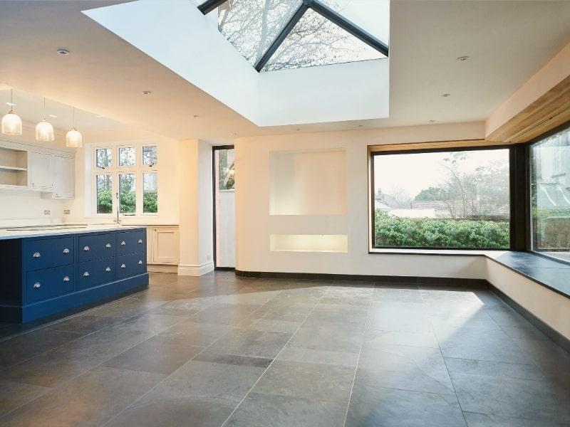 agrandissement d une maison avec cuisine bleue et toit en verre